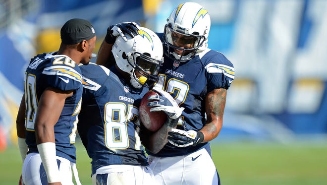 San Diego Chargers wide receiver Michael Spurlock (87) is congratulated by wide receiver Robert Meachem (right) and cornerback Antoine Cason (20) after running the opening kickoff back 99 yards for a touchdown.
