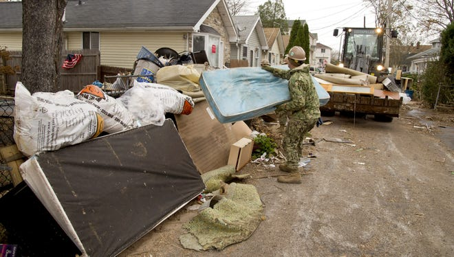 A volunteer from Gulfport, Miss., loads a bulldozer with debris that was caused by Hurricane Sandy during relief efforts in Staten Island, N.Y., ahead of a forecasted storm.