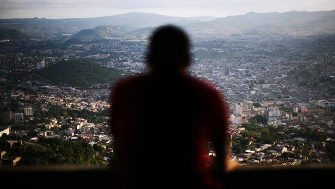 A man looks toward Tegucigalpa, the capital city of Honduras, from the Picacho National Park. This capital of 1.3 million people is a lawless place, but it does seem to have its own set of unwritten rules for living with the daily dangers.