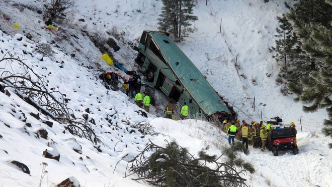Emergency personnel respond to the scene of a multiple-fatality accident where a tour bus careened through a guardrail along an icy highway and several hundred feet down a steep embankment.