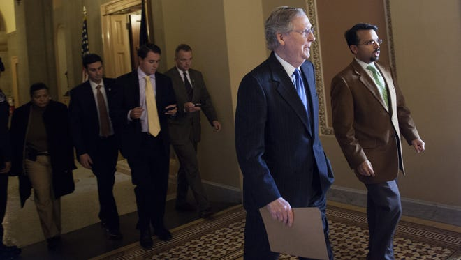 Senate Minority Leader Mitch McConnell, R-Ky., walks with an aide toward the Senate Chamber on Sunday on Capitol Hill.