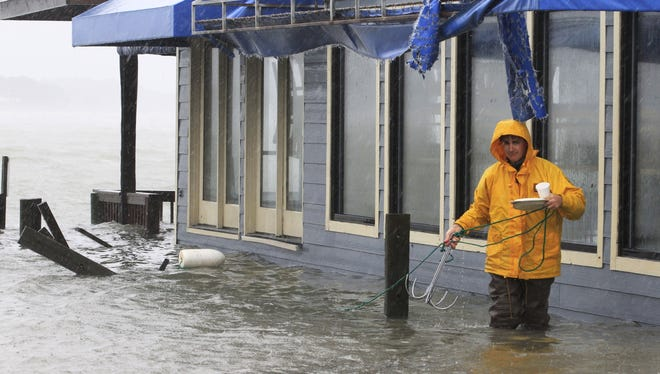 A worker retrieves a grappling hook on the dock next to Bubba's restaurant on the water in Virginia Beach, Va.
