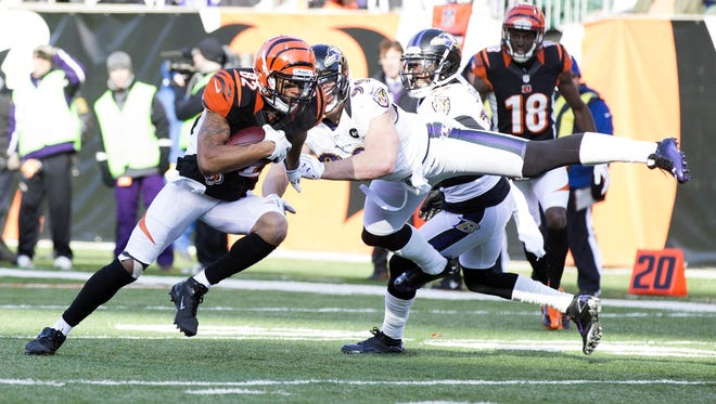 Ravens outside linebacker Paul Kruger (99) misses a tackle as Bengals wide receiver Marvin Jones (82) heads for the end zone at Paul Brown Stadium.