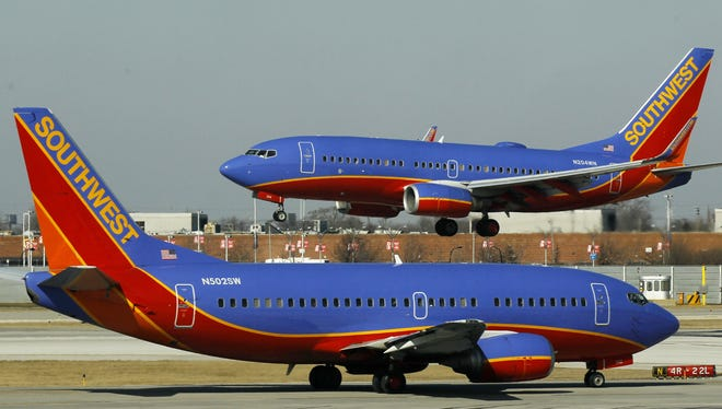 A Southwest Airlines Boeing 737 waits to take off at Chicago's Midway Airport as another lands.