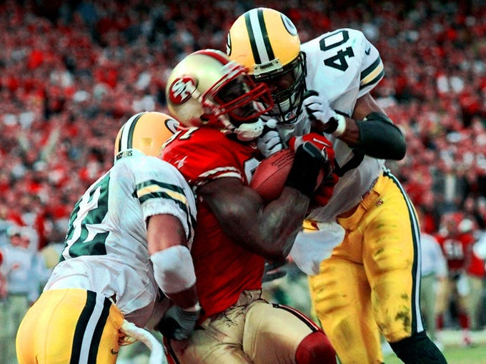 Terrell Owens (pictured) had a case of the dropsies all day during a 1998 NFC Wild Card game, but Steve Young didn't give up on him. With the 49ers needing a touchdown, Young threw over the middle to Owens, who caught the game-winning 25-yard touchdown sandwiched between two Packers defenders for a 30-27 win.