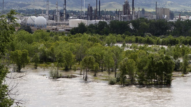 The Yellowstone River flows past the Exxon Mobil refinery in Billings, Mont., on July 6, 2011. An Exxon pipeline near Laurel, Mont., ruptured and spilled crude into the river.