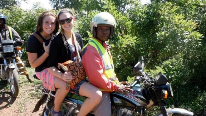Tori Hogendorf and Meagan Neis, University of Wisconsin students, ride to an isolated Maasai community at the border of Kenya and Tanzania in June.