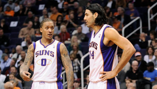Phoenix Suns forward Michael Beasley (0) and forward Luis Scola (14) talk on the court. Beasley has been struggling after signing a big contract with the Suns.