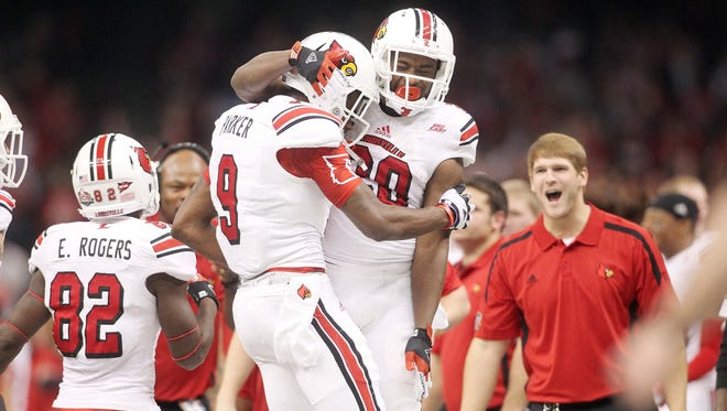 Louisville Cardinals wide receiver DeVante Parker (9) and running back Corvin Lamb (20) celebrates a touchdown against the Florida Gators during the second quarter of the Sugar Bowl at the Mercedes-Benz Superdome.