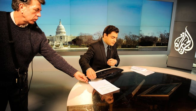 Floor manager Ron Ferry hands notes to Al Jazeera network anchor Shihab Rattansi at the Al Jazeera English language channel studio in Washington in March.
