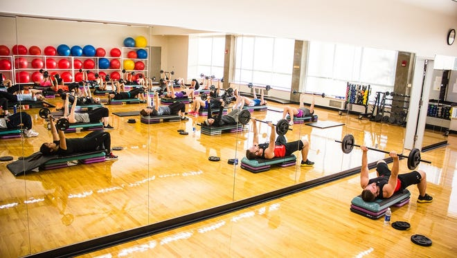 Oregon State University exercise science student Jacob Taskinen leads a body pump class.