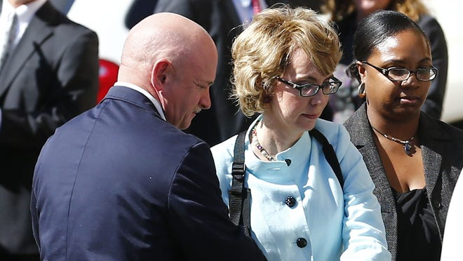 Former U.S. Rep. Gabrielle Giffords is escorted from court by her husband Mark Kelly on Nov. 8.