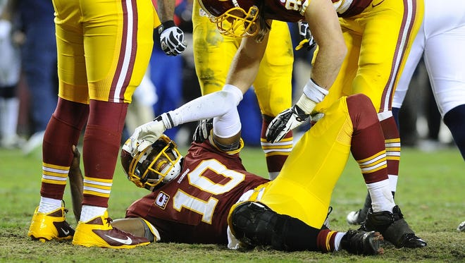 Washington Redskins quarterback Robert Griffin III reacts after getting injured during the fourth quarter of the NFC wild-card playoff game against the Seattle Seahawks at FedEx Field.