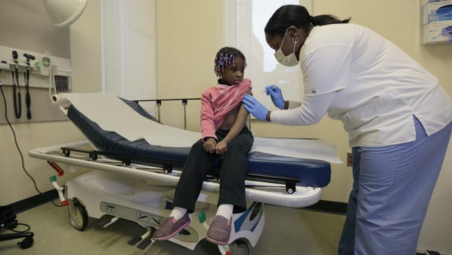 Four-year-old Gabriella Diaz sits as registered nurse Charlene Luxcin, right, administers a flu shot Wednesday at the Whittier Street Health Center in Boston.