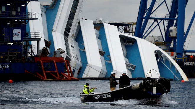 Workers pass on a small boat near the Costa Concordia in January.