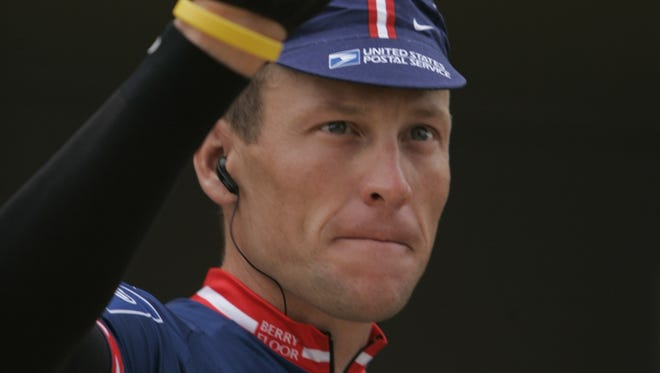 Lance Armstrong waves to the crowd after the sign-in ceremony before the start of the 2004 Tour de France.