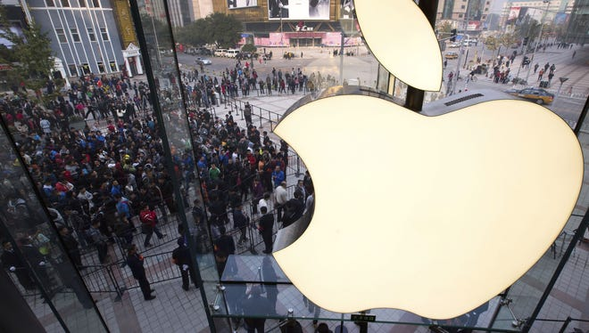 People line up to enter a newly-opened Apple Store in Wangfujing shopping district in Beijing last October.