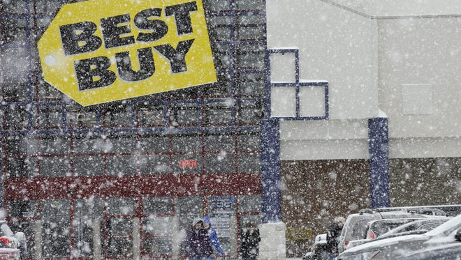 People walk in the parking lot of a Best Buy store during a snow storm in North Olmsted, Ohio, Dec. 26, 2012.