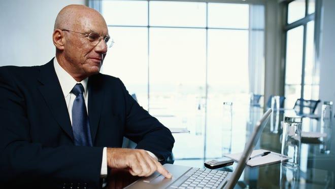 Senior businessman using laptop.