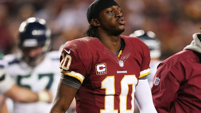 Robert Griffin III of the Washington Redskins leaves the field injured during their 24 to 14 loss to the Seattle Seahawks in the NFC Wild Card Playoff Game at FedExField on January 6, 2013 in Landover, Maryland. Griffin was injured during the game and underwent knee surgery Tuesday.