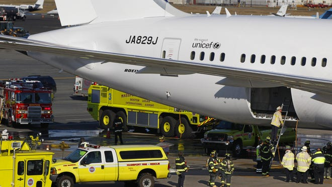 A Japan Airlines Boeing 787 Dreamliner is surrounded by emergency vehicles Jan. 7 at Boston's Logan Airport, after a small electrical fire was reported 15 minutes after the plane had landed.