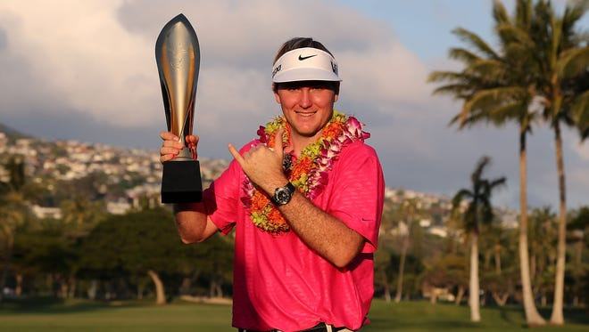 Russell Henley poses with the championship trophy Sunday after winning the Sony Open in record-setting fashion. His victory earned him an invitation to the Masters.
