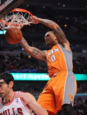 Suns forward Michael Beasley dunks over Bulls guard Kirk Hinrich during Saturday's 97-81 win.