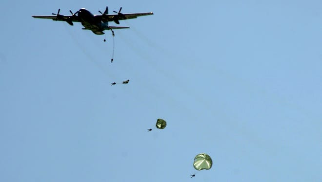 Navy SEAL Qualification Training students parachute out of a C-130 Hercules military transport aircraft during a routine training exercise over San Diego Bay.