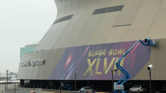 A person works on the Super Bowl sign at the Superdome in New Orleans on Monday, Jan. 14, 2013.