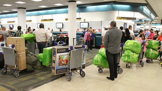 Travelers leaving Miami International Airport on charter flights for Havana, Cuba, bring as much goods as allowed to the island for family members. Luggage is wrapped and ready to go as they make their way to the ticket counters.