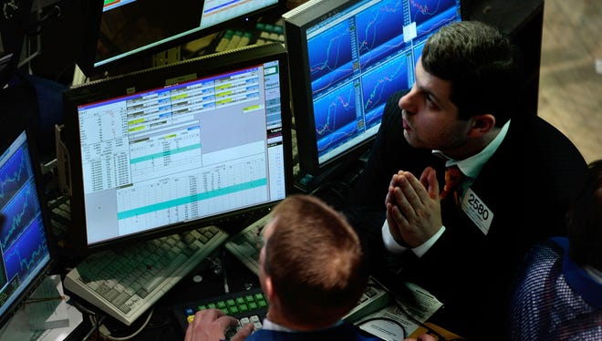 A financial professional looks up at monitors at his station on the floor of the New York Stock Exchange.