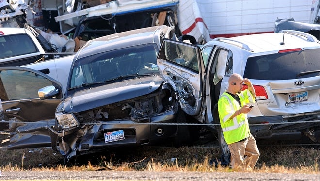 An emergency worker walks past a pile of cars from an accident in Texas on Nov. 22.