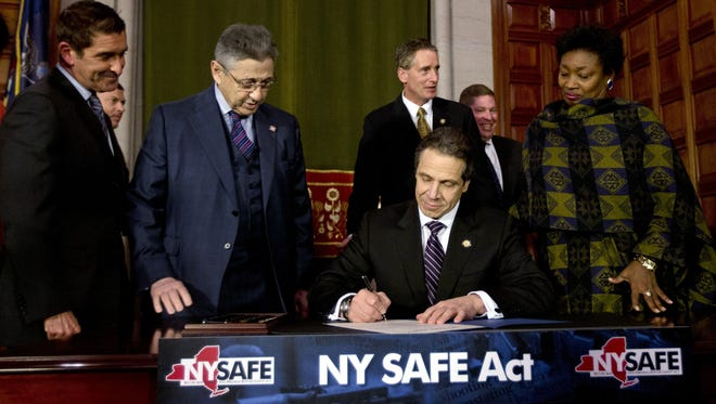 New York Gov. Andrew Cuomo signs New York's Secure Ammunition and Firearms Enforcement Act into law during a ceremony in the Red Room at the Capitol on Tuesday.