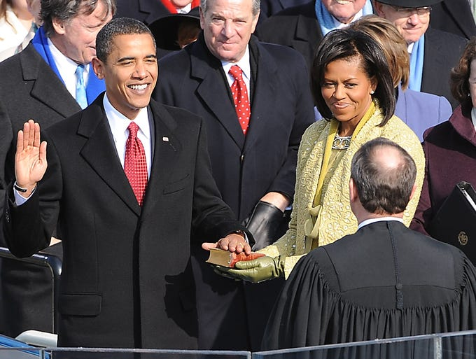 Barack Obama, left, joined by his wife, Michelle, takes the oath of office from Supreme Court Chief Justice John Roberts as he becomes the 44th president of the United States on Jan. 20, 2009, at the Capitol in Washington.