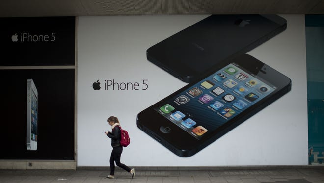 A woman walks past an advertisement for the Apple iPhone 5 in London.