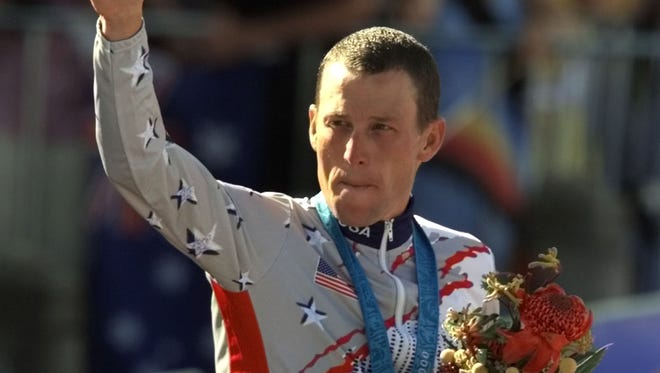 This Sept. 30, 2000, file photo shows U.S. cyclist Lance Armstrong waving after receiving the bronze medal in the men's individual time trials at the Summer Olympics in Sydney.