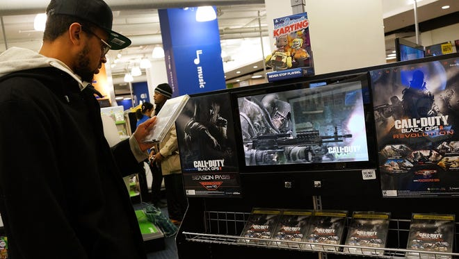 A man looks at a copy of the game Call of Duty: Black Ops II at an electronics store in New York City.