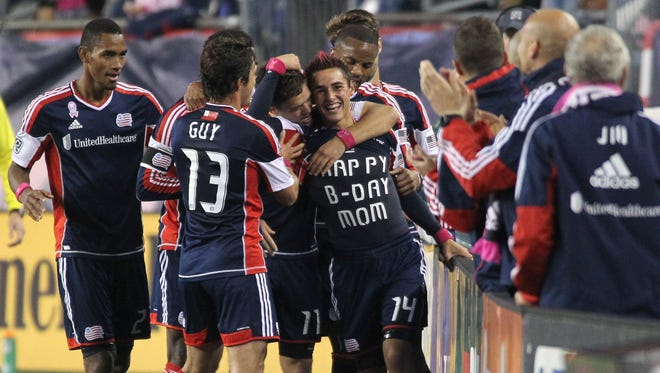 New England Revolution forward Diego Fagundez celebrates a goal with his teammates and shows off his under shirt during the first half against the Chicago Fire at Gillette Stadium.