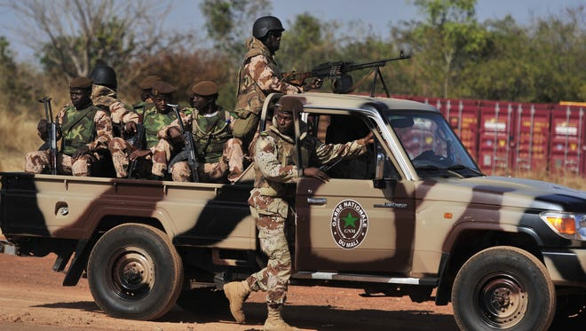 Malian National guards patrol a military airbase in Bamako as President Dioncounda Traore visits French troops.