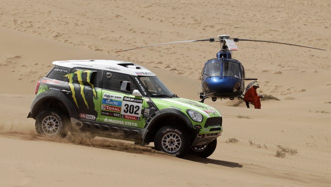 Stephane Peterhansel and Jean Paul Cottret, both of France, race their Mini past a helicopter parked on a dune during the 12th stage of the 2013 Dakar Rally.