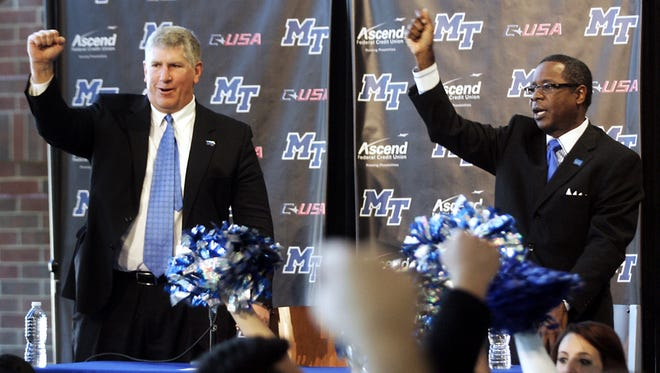 Middle Tennessee director of athletics Chris Massaro, left, and President Sydney McPhee stand for the school's fight song during a news conference, Thursday, Nov. 29, 2012, in Murfreesboro, Tenn. Middle Tennessee and Florida Atlantic will join Conference USA, leaving the Sun Belt as part of the ever-changing college landscape. (AP Photo/The Daily News Journal, John Gillis) NO SALES ORG XMIT: TNMUR502