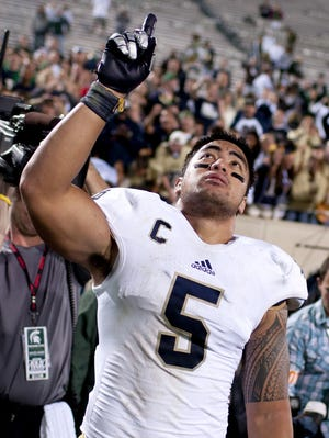 Manti Te'o points to the sky as he leaves the field after Notre Dame's win over Michigan State on Sept. 15, his first game after learning of Kekua's death.