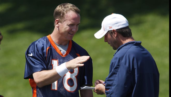 Denver Broncos quarterback Peyton Manning, left, jokes with quarterbacks coach Adam Gase during an NFL football practice at the team's training facility in Englewood, Colo., on Thursday,  June 14, 2012.