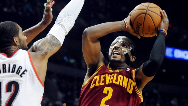 Cleveland Cavaliers point guard Kyrie Irving  shoots the ball over Portland Trail Blazers power forward LaMarcus Aldridge during the first quarter of the game at the Rose Garden.
