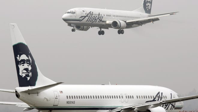 In this Jan. 17, 2009 file photo, an Alaska Airlines jet lands as another taxis for takeoff at Seattle-Tacoma International Airport.