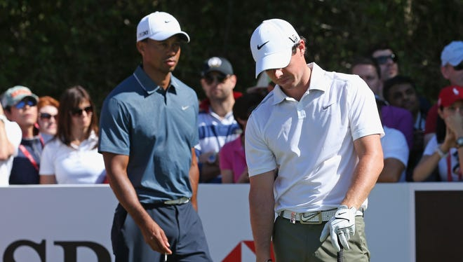 Rory McIlroy of Northern Ireland reacts to a poor shot as Tiger Woods of the USA looks on.