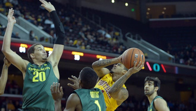 Southern California Trojans guard Jio Fontan is defended by Oregon Ducks players Waverly Austin, left, Dominic Artis, center, and Arsalan Kazemi at the Galen Center. Oregon defeated USC 76-74.