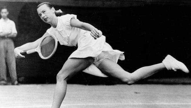 """Gertrude Gussie Moran races across Centre Court in a third-round women's singles match in Wimbledon, England, on June 22, 1949.  Moran wears a short tennis dress with ruffled, lace-trimmed briefs showing below the hem.  The tennis outfit, designed and sewn by former tennis player-turned-fashion designer Teddy Tinling, earned her the nickname """"Gorgeous Gussie."""""""