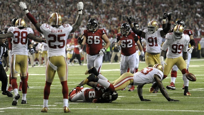 49ers players react after NaVorro Bowman (53) stops Falcons wide receiver Roddy White (84) on fourth down during the fourth quarter of the NFC Championship Game at the Georgia Dome. The 49ers won 28-24.