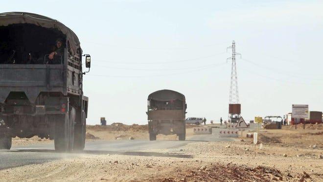 Algerian army trucks drive on a road near the gas plant on Jan 20.